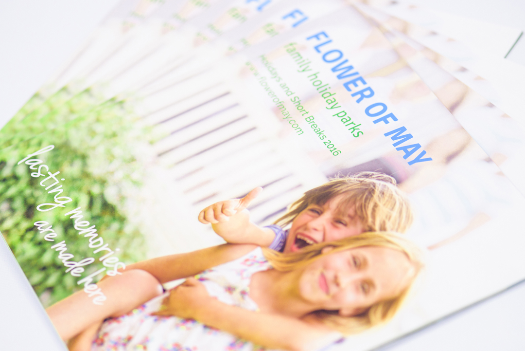 Flower of May holiday park brochure cover with two smiling children